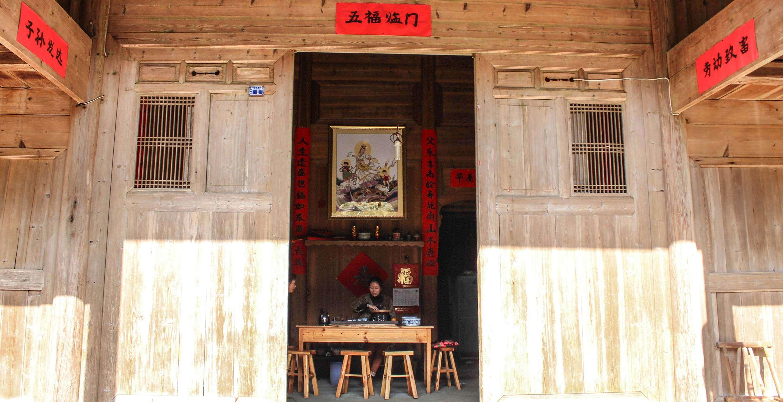 Li Xiangxi brews tea at her family's home in Tongmu