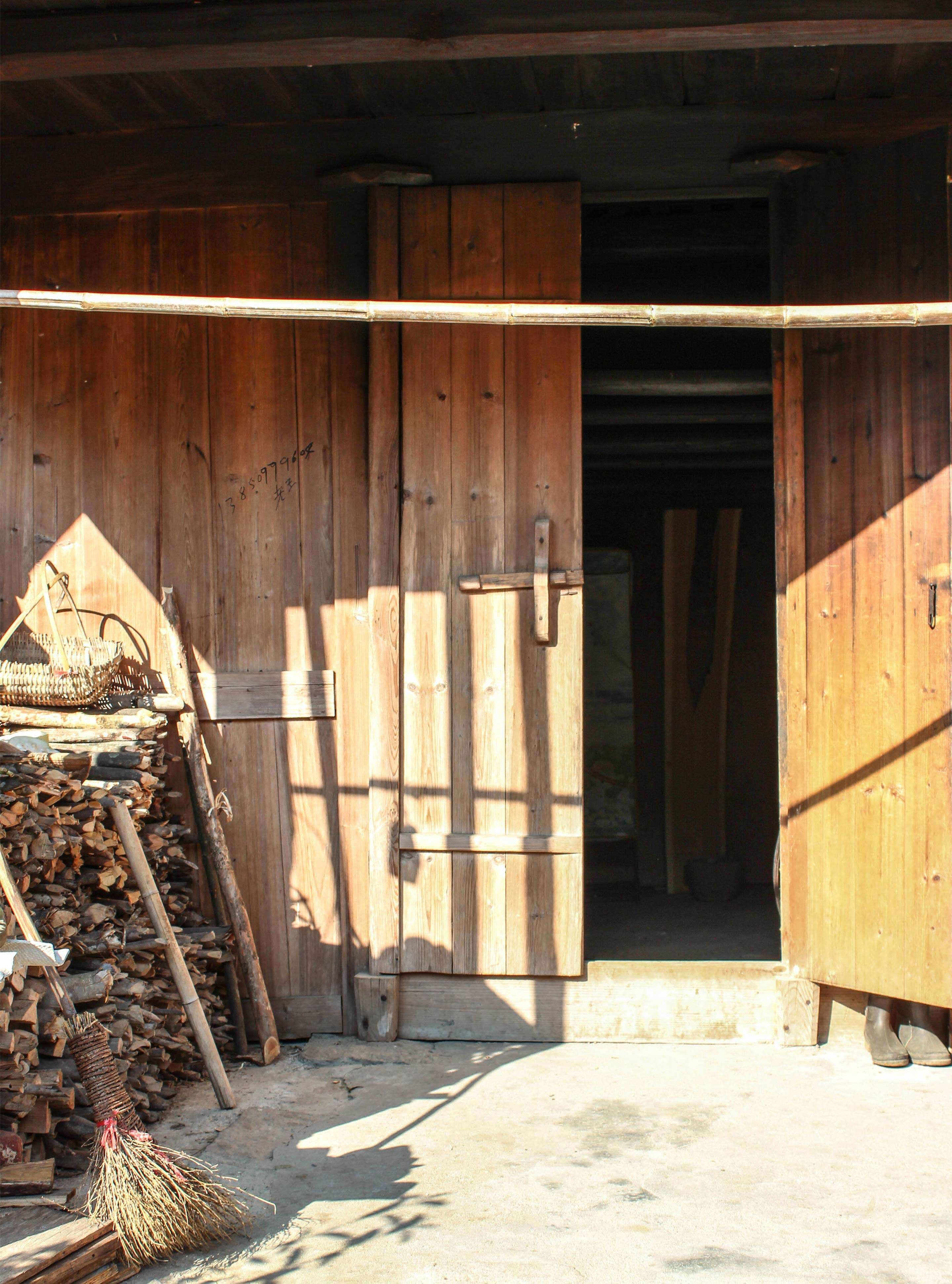 Dried wood is stacked neatly next to the room where the Li Family smokes their black tea