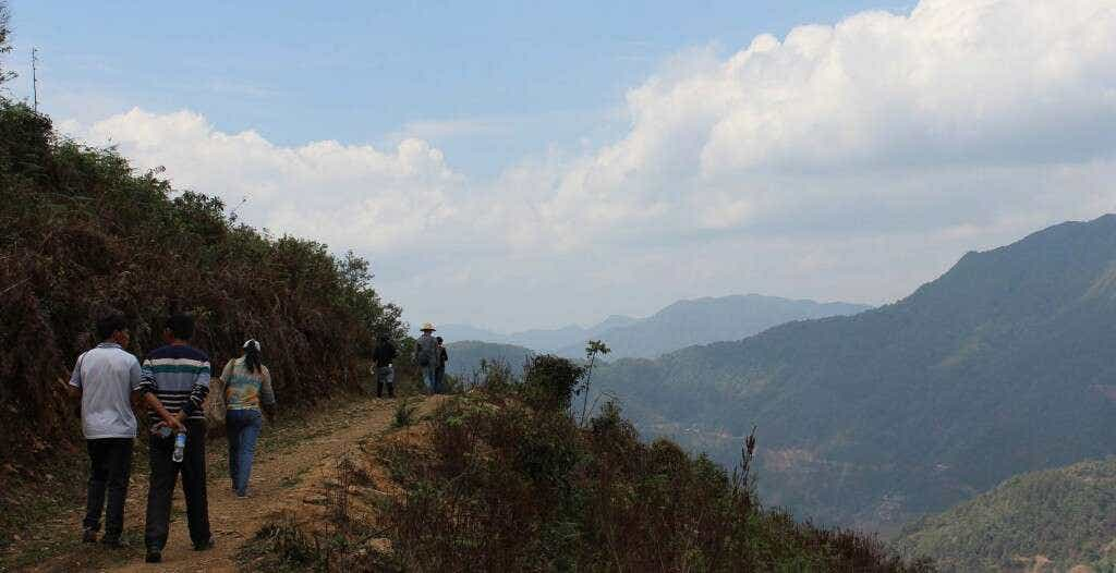 Master Zhou and his student Mr. Deng walk down a road built by Mr. Deng himself to allow his truck to carry fresh picked tea back to his workshop faster.
